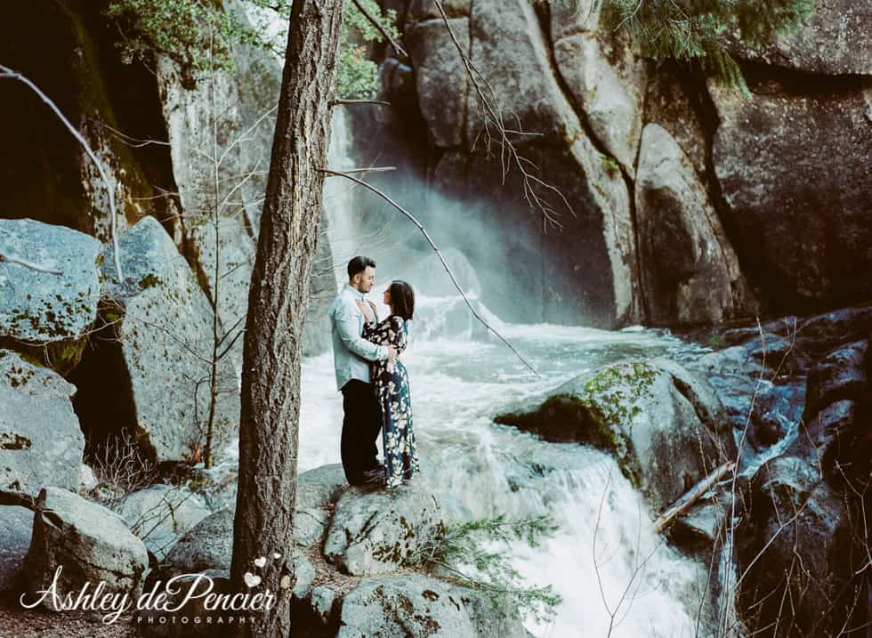 Man and woman standing by a waterfall
