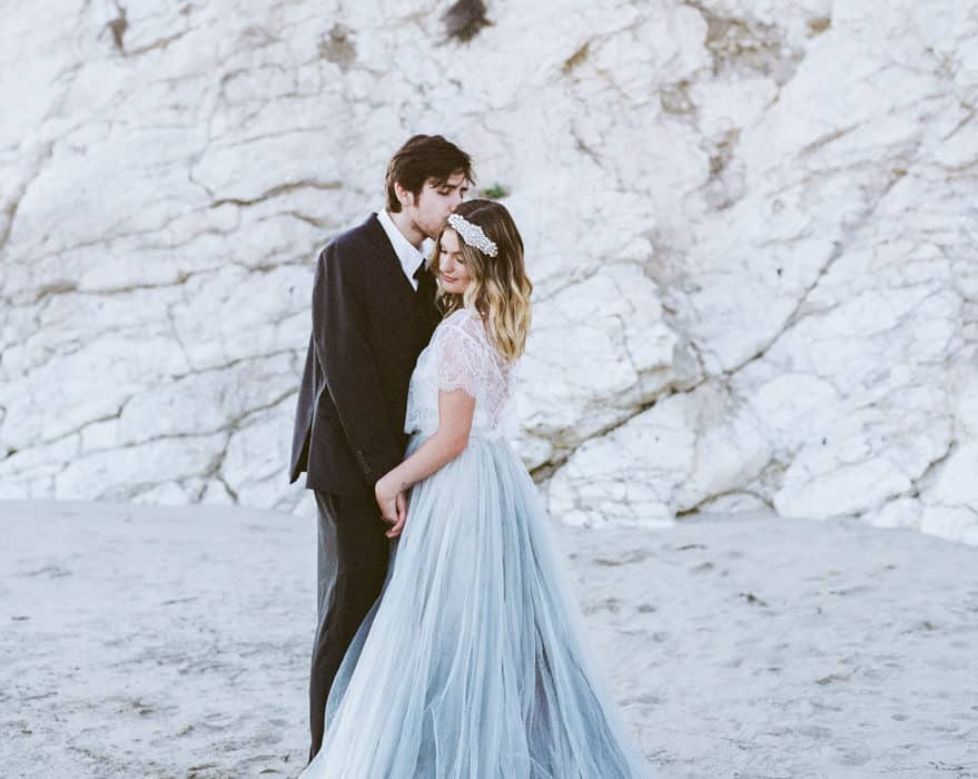 Bride and groom standing on the beach
