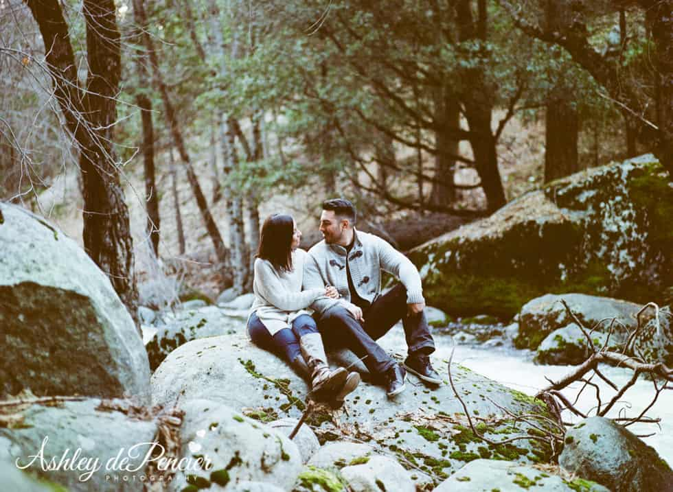 A couple sitting outside on some rocks