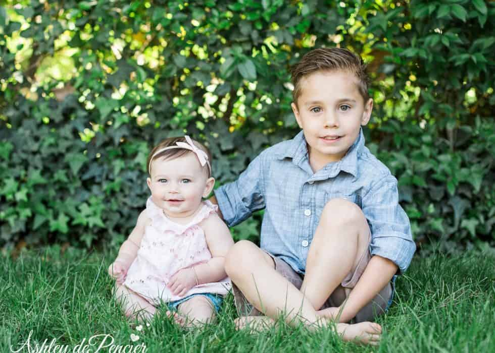 Brother and sister sitting in the grass