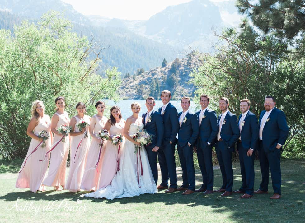 Bridal party standing by a lake